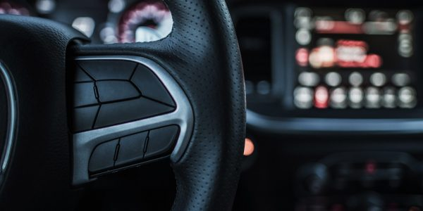 Driver and the Vehicle. Driving Concept. Modern Car Steering Wheel Covered By Leather and Multimedia Dashboard in the Background.